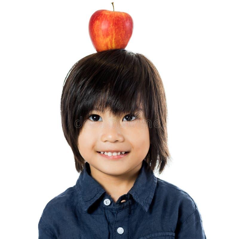 Pequeño muchacho asiático con la manzana en la cabeza fotos de archivo