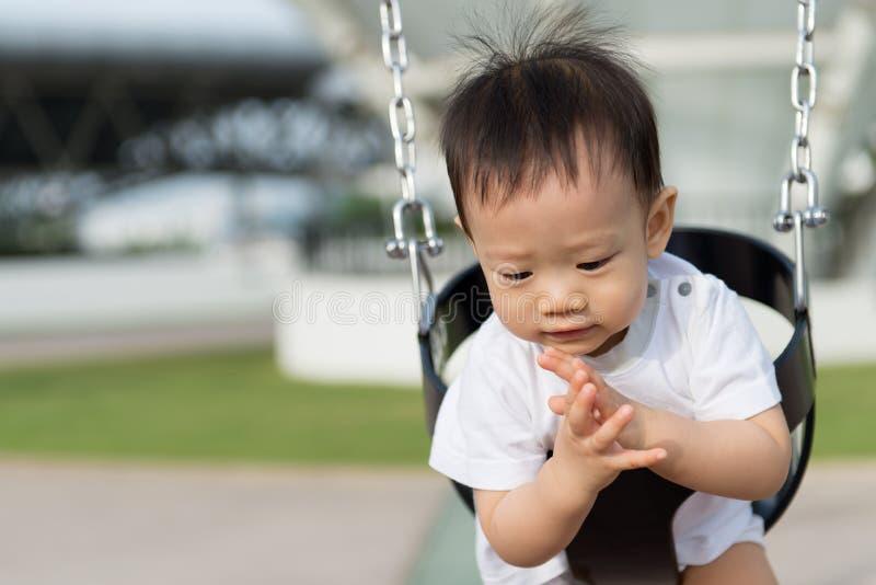 Pequeño muchacho asiático en el oscilación imagenes de archivo