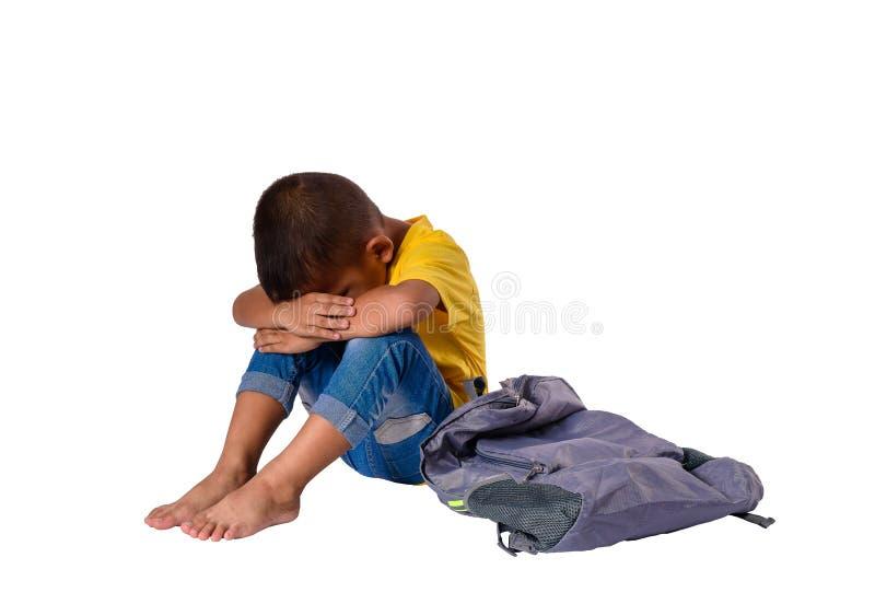 Pequeño muchacho asiático triste que se sienta en piso con la mochila aislada en el fondo blanco con la trayectoria de recortes E foto de archivo