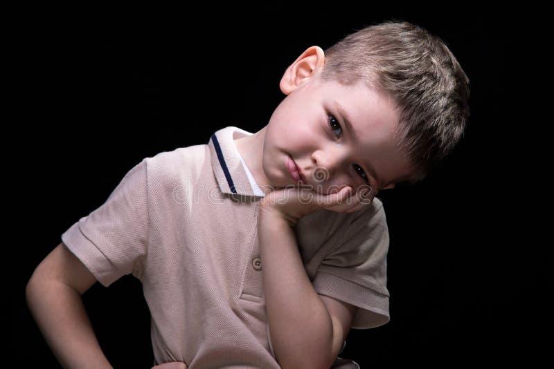 Pequeño muchacho cansado con las manos en caderas, cierre para arriba imagen de archivo