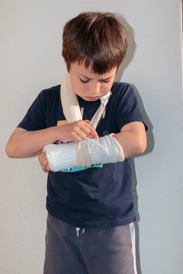 Pequeño muchacho caucásico con el brazo quebrado imagenes de archivo