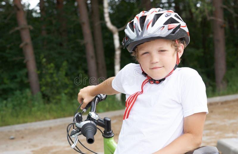 Pequeño muchacho caucásico en los soportes protectores del casco que se inclinan en la bici que presenta para la cámara Adolescen fotos de archivo libres de regalías