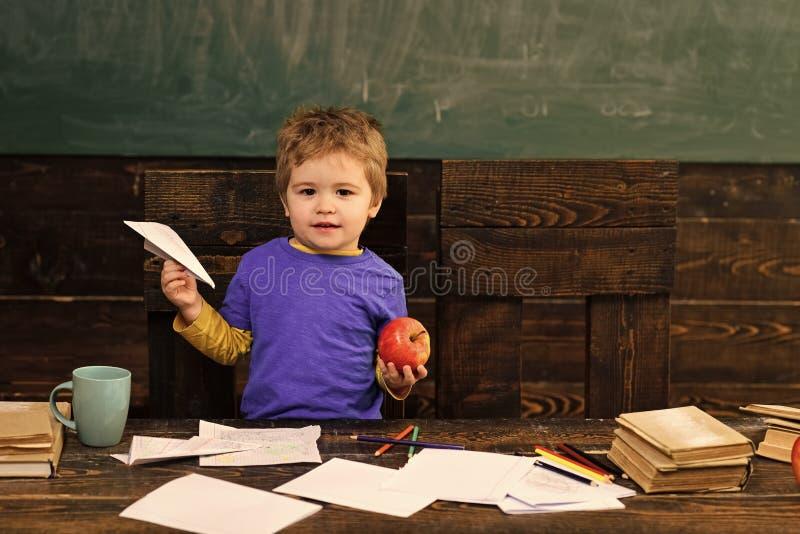 Pequeño muchacho con el avión de papel y manzana en sala de clase Niño en la escuela primaria Niño lindo detrás de la tabla con l fotos de archivo libres de regalías