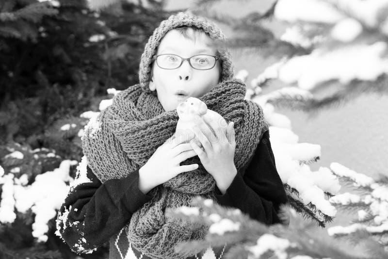 Pequeño muchacho con el moneybox en el invierno al aire libre foto de archivo