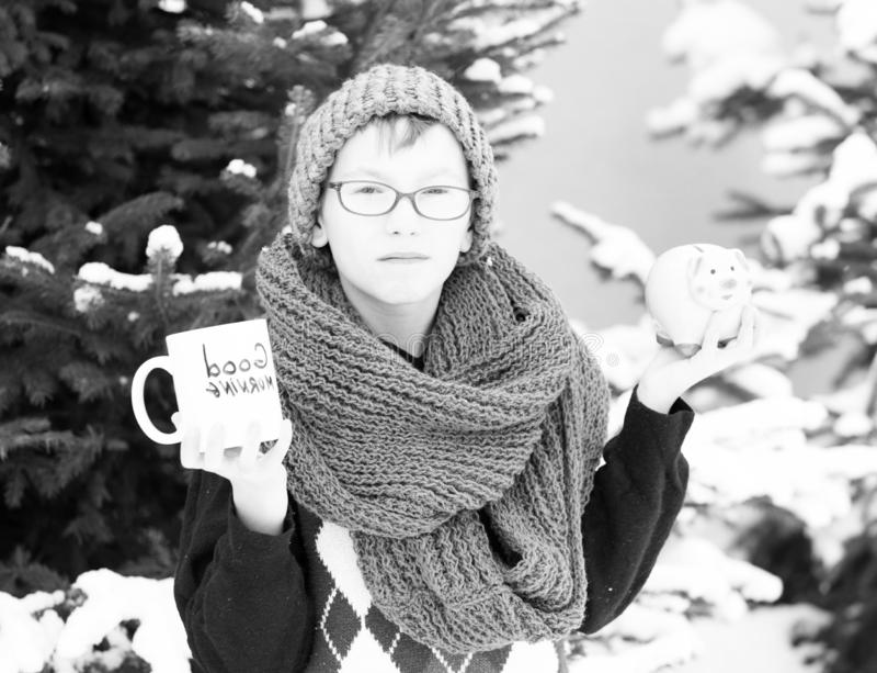 Pequeño muchacho con la taza y moneybox en el invierno al aire libre foto de archivo libre de regalías