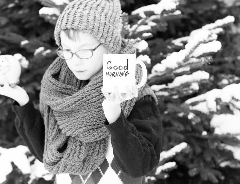 Pequeño muchacho con la taza y moneybox en el invierno al aire libre fotografía de archivo libre de regalías