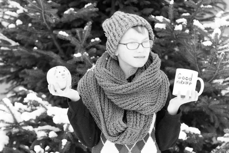 Pequeño muchacho con la taza y moneybox en el invierno al aire libre fotos de archivo libres de regalías