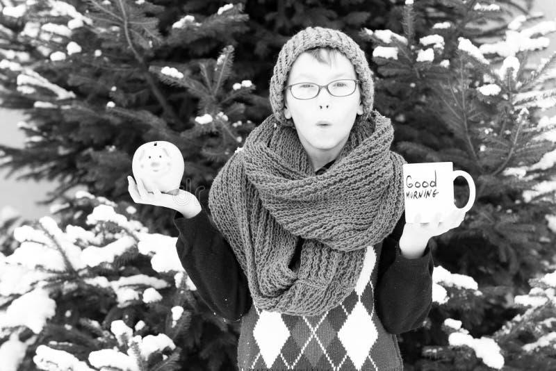 Pequeño muchacho con la taza y moneybox en el invierno al aire libre imágenes de archivo libres de regalías
