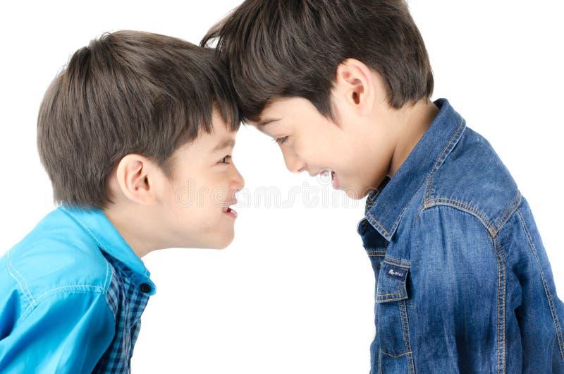 Pequeño muchacho del hermano que lucha en el fondo blanco imagen de archivo