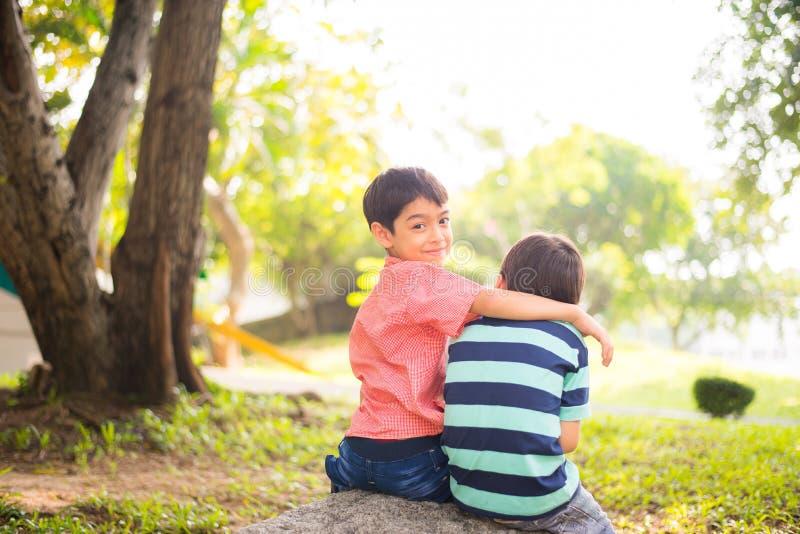 Pequeño muchacho del hermano que se sienta junto en el parque al aire libre foto de archivo libre de regalías