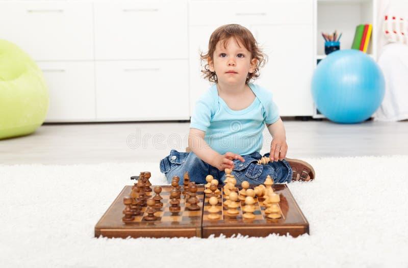 Pequeño muchacho del niño con la tarjeta de ajedrez imagenes de archivo