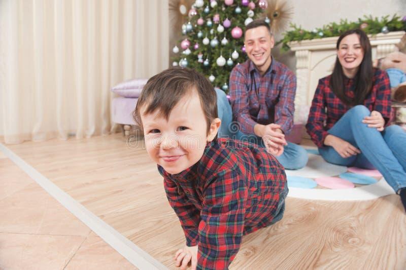Pequeño muchacho divertido con los padres felices durante la tarde de la Navidad cerca imágenes de archivo libres de regalías