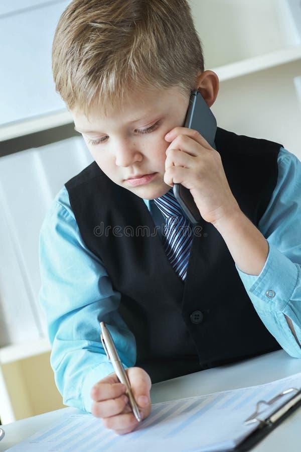 Pequeño muchacho ejecutivo confiado del jefe del hombre de negocios que hace notas y negociaciones en el teléfono que se sienta e foto de archivo libre de regalías
