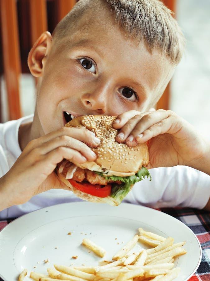Pequeño muchacho lindo 6 años con la hamburguesa y las patatas fritas que hacen caras locas fotografía de archivo