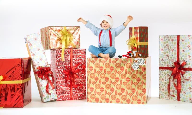 Pequeño muchacho lindo en el un montón de presentes fotos de archivo libres de regalías