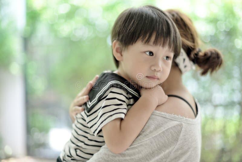 Pequeño muchacho lindo que abraza a su madre fotografía de archivo