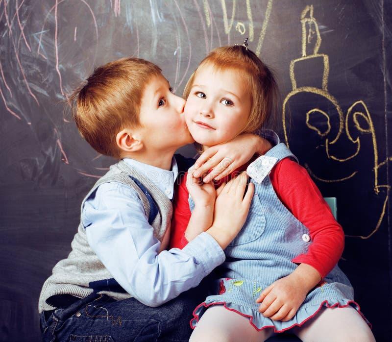 Pequeño muchacho lindo que besa a la muchacha rubia en sala de clase en la pizarra, primer amor de la escuela, concepto de la gen fotos de archivo