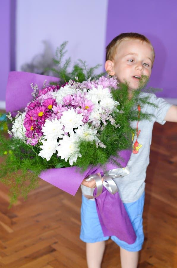 Pequeño muchacho lindo que da las flores imagen de archivo
