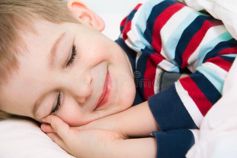 Pequeño muchacho lindo que duerme en cama imagen de archivo