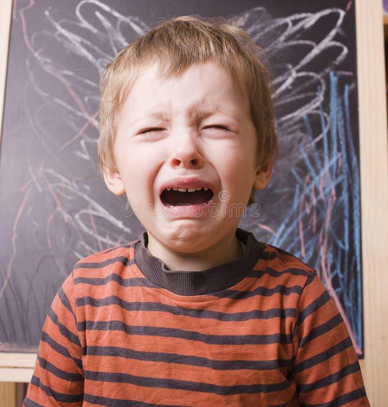 Pequeño muchacho lindo que grita y que llora en la escuela imágenes de archivo libres de regalías