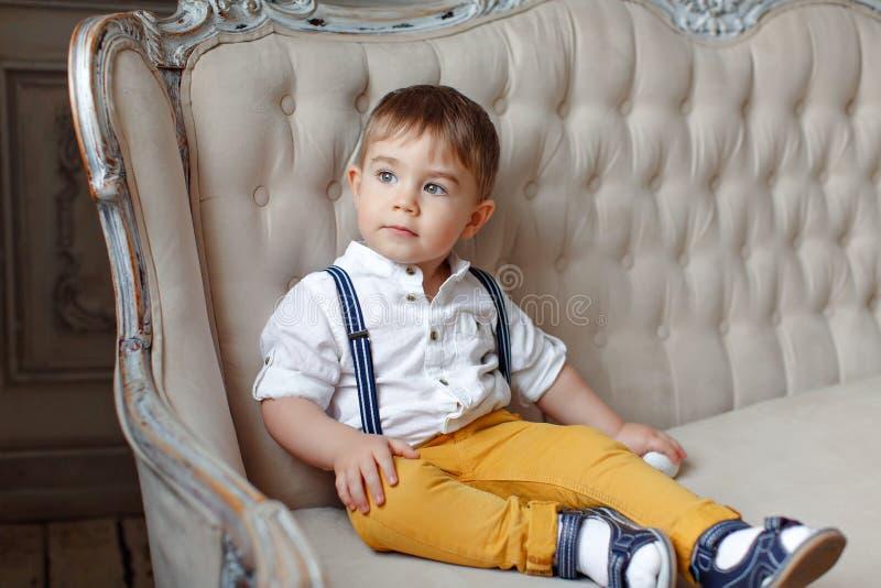 Pequeño muchacho muy lindo en pantalones amarillos y ligas que se sientan en a imagen de archivo libre de regalías