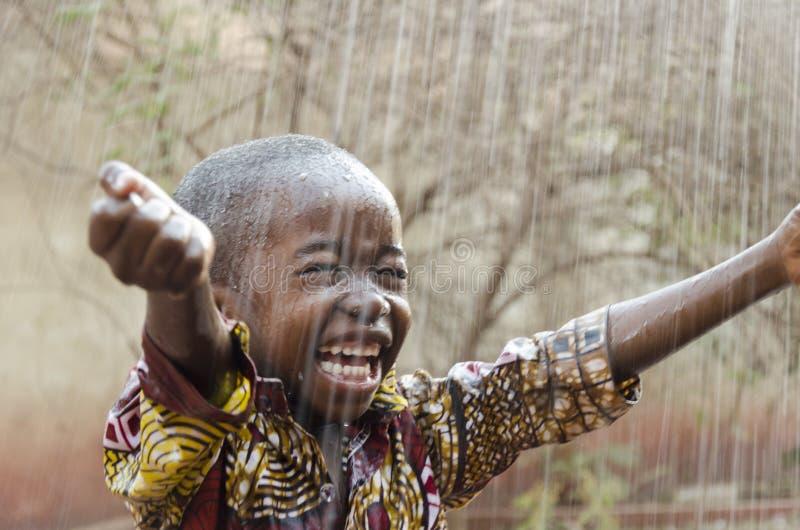 Pequeño muchacho negro africano nativo que se coloca al aire libre debajo del agua de lluvia para el símbolo de África fotos de archivo