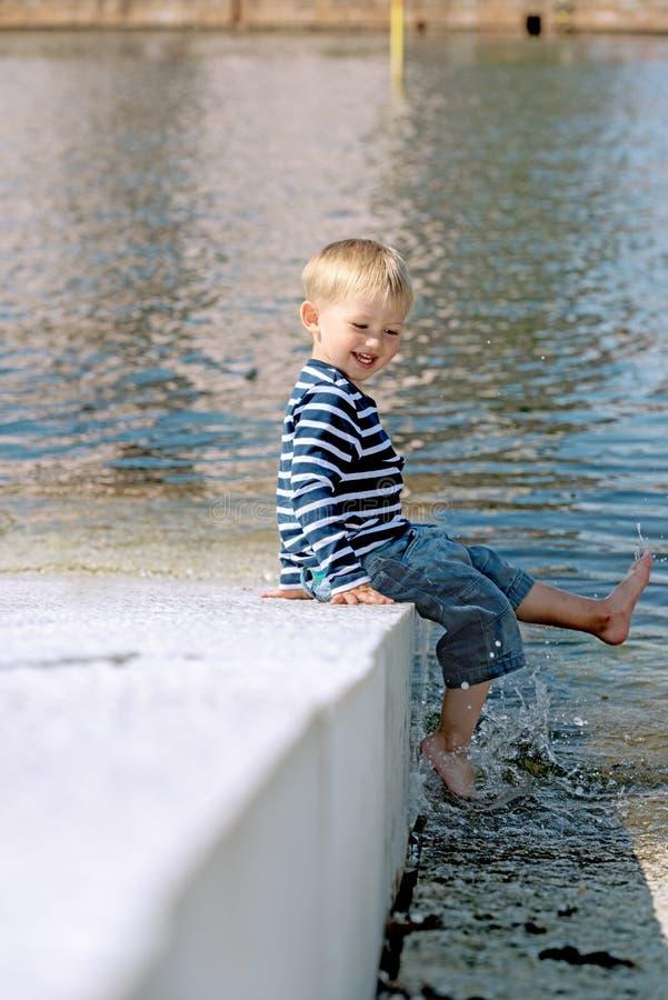 Pequeño muchacho preescolar que juega al aire libre cerca del agua fotografía de archivo libre de regalías
