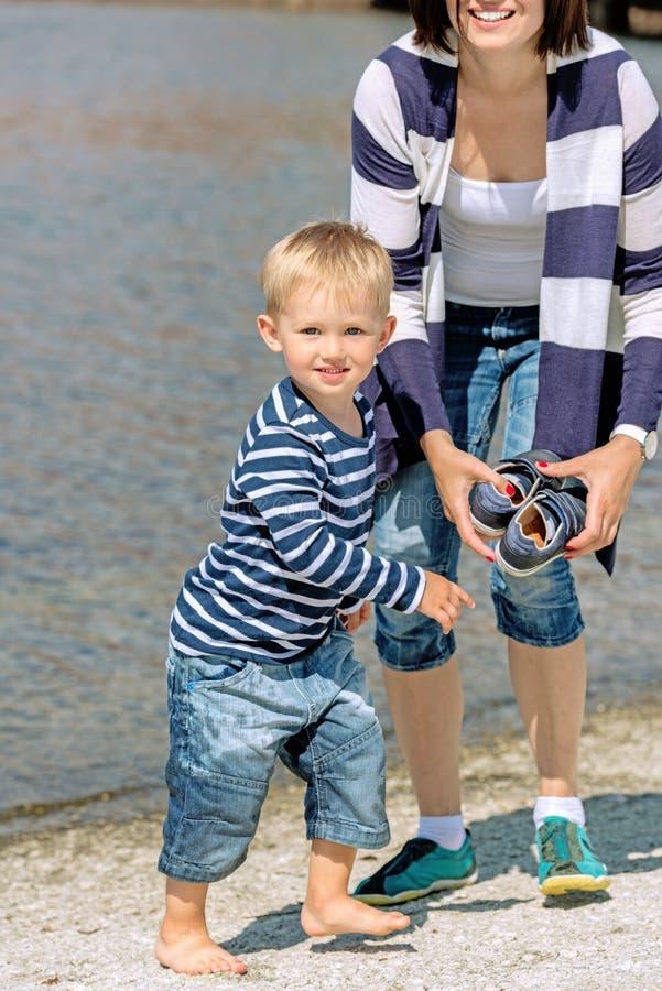 Pequeño muchacho preescolar que juega en la playa con la madre fotografía de archivo