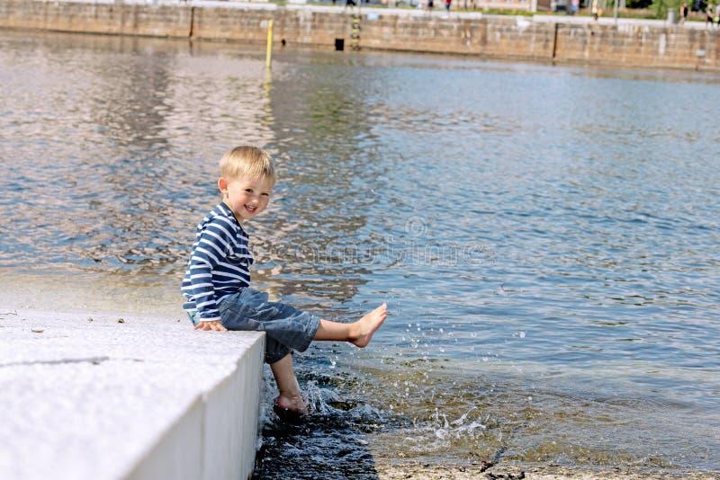 Pequeño muchacho preescolar que presenta en pies de la playa al aire libre fotografía de archivo libre de regalías