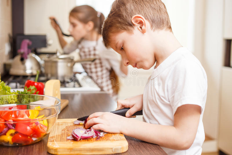 Pequeño muchacho que cocina así como su hermana fotografía de archivo libre de regalías