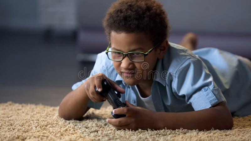 Pequeño muchacho que juega al videojuego que miente en piso en casa, competencia en línea, resto fotos de archivo