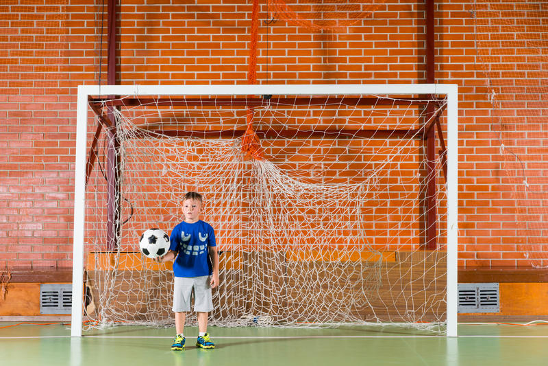 Pequeño muchacho que juega a fútbol en una corte interior fotos de archivo libres de regalías