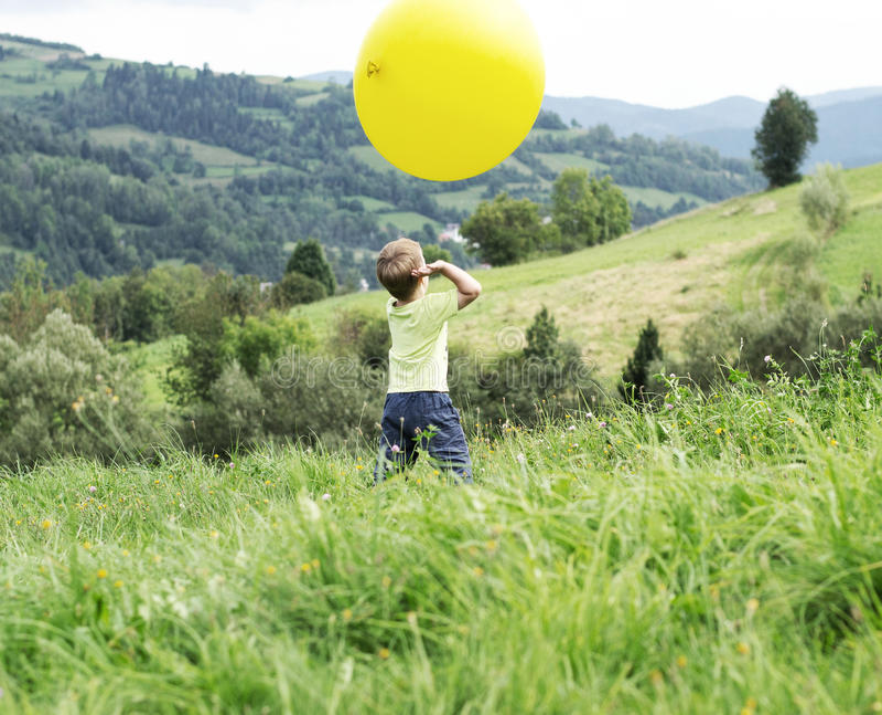 Pequeño muchacho que juega un globo enorme imagen de archivo