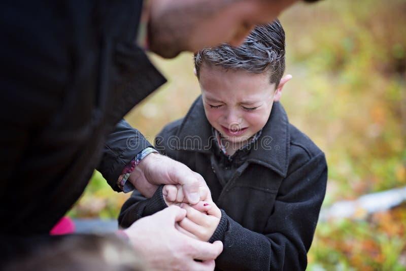 Pequeño muchacho que llora en el dolor que hiere su mano El padre proporciona los primeros auxilios fotos de archivo libres de regalías