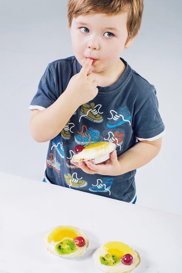Pequeño muchacho que prueba la torta de la fruta imágenes de archivo libres de regalías