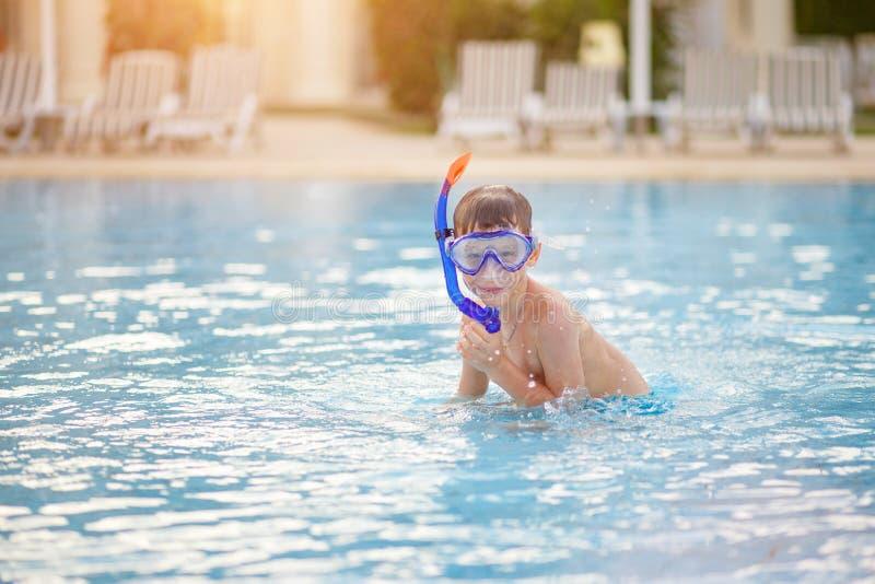 Pequeño muchacho que se divierte con la máscara en piscina imágenes de archivo libres de regalías