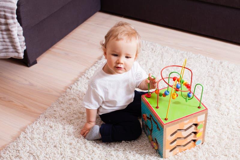 Pequeño muchacho que se sienta en una manta suave con el juguete en sus brazos imágenes de archivo libres de regalías
