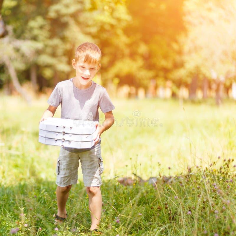 Pequeño muchacho que trae la caja tres de pizza para una comida campestre fotos de archivo libres de regalías