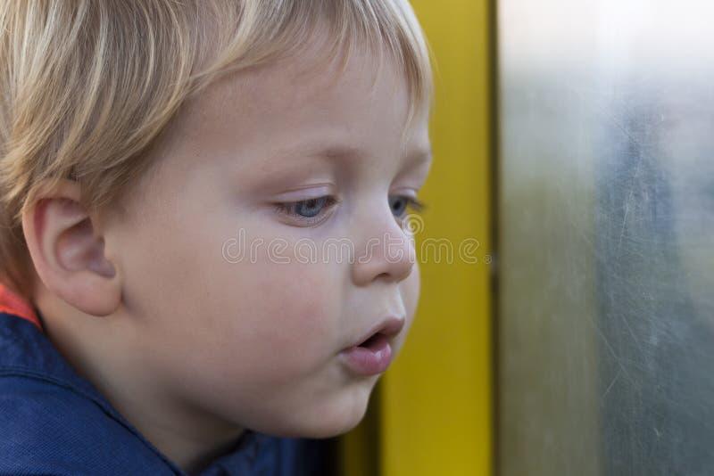Pequeño muchacho rubio adorable del niño que se sienta cerca de ventana y que parece exterior fotografía de archivo libre de regalías