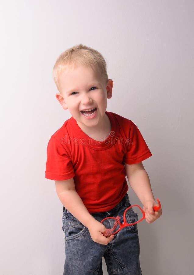 Pequeño muchacho rubio de risa en camisa roja foto de archivo