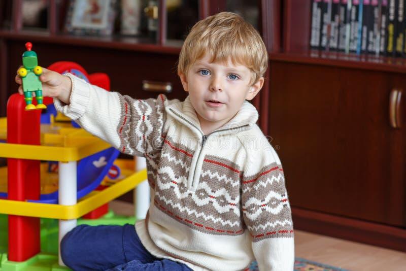 Pequeño muchacho rubio de tres años que juegan con los juguetes en casa foto de archivo