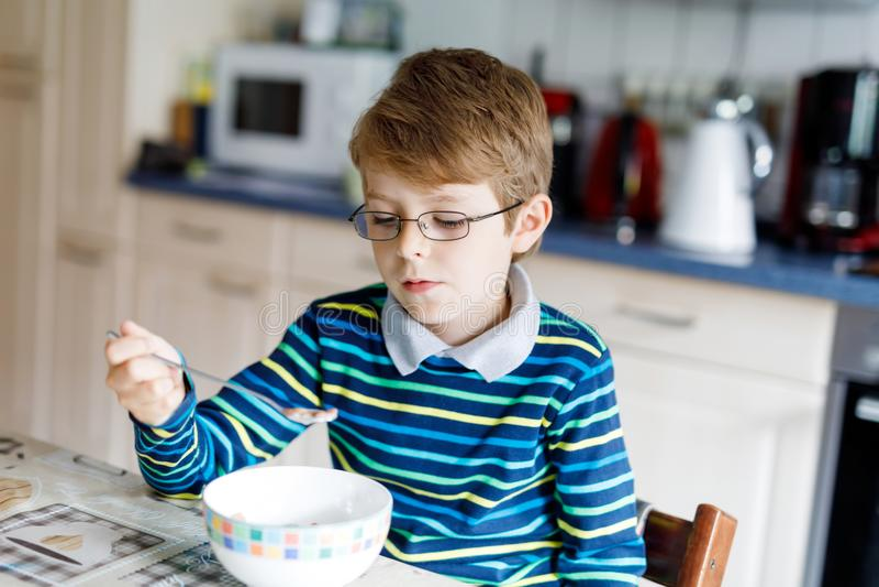 Pequeño muchacho rubio feliz del niño que come los cereales para el desayuno o el almuerzo Consumición sana para los niños fotografía de archivo