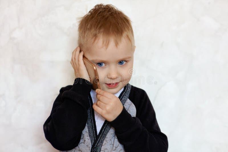 Pequeño muchacho rubio lindo con negociaciones de ojos azules sobre el teléfono móvil, sonriendo Ni?os y concepto moderno de la t fotografía de archivo libre de regalías