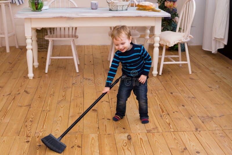 Pequeño muchacho rubio que barre el piso en la cocina Las viejas ayudas de los yers bonitos del muchacho 3 parents con quehacer d imagen de archivo libre de regalías