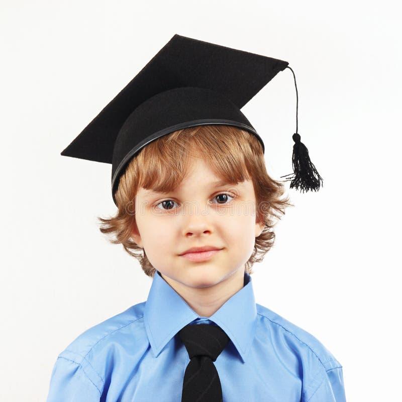 Pequeño muchacho serio en sombrero académico en el fondo blanco imagen de archivo libre de regalías