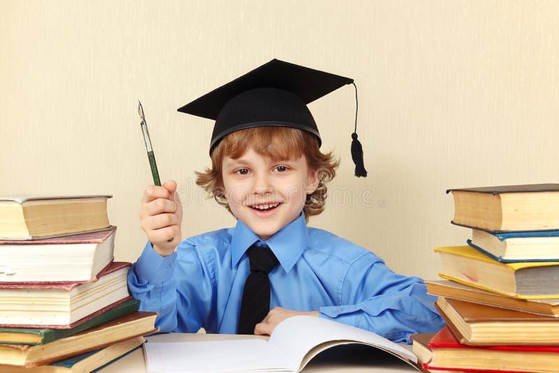 Pequeño muchacho sonriente en sombrero académico con la pluma de la rareza entre los libros viejos fotografía de archivo libre de regalías