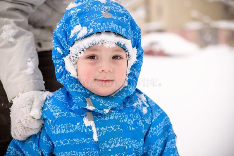 Pequeño muchacho sonriente feliz al aire libre en la nieve en ropa del invierno El niño tiene una helada en su cara fotos de archivo libres de regalías
