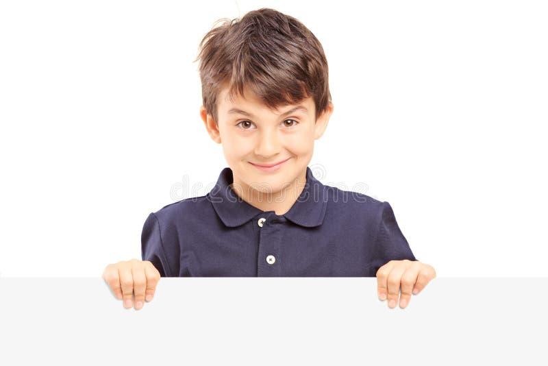 Pequeño muchacho sonriente que se coloca detrás de un panel en blanco fotos de archivo libres de regalías