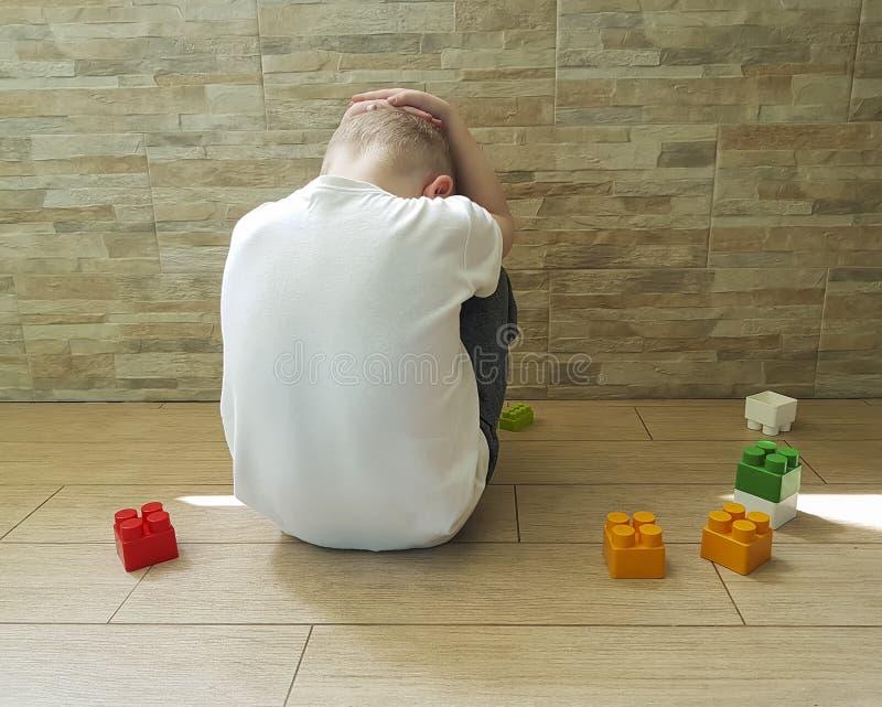 Pequeño muchacho triste que se sienta en el piso con una depresión del bloque frustrada imagen de archivo libre de regalías