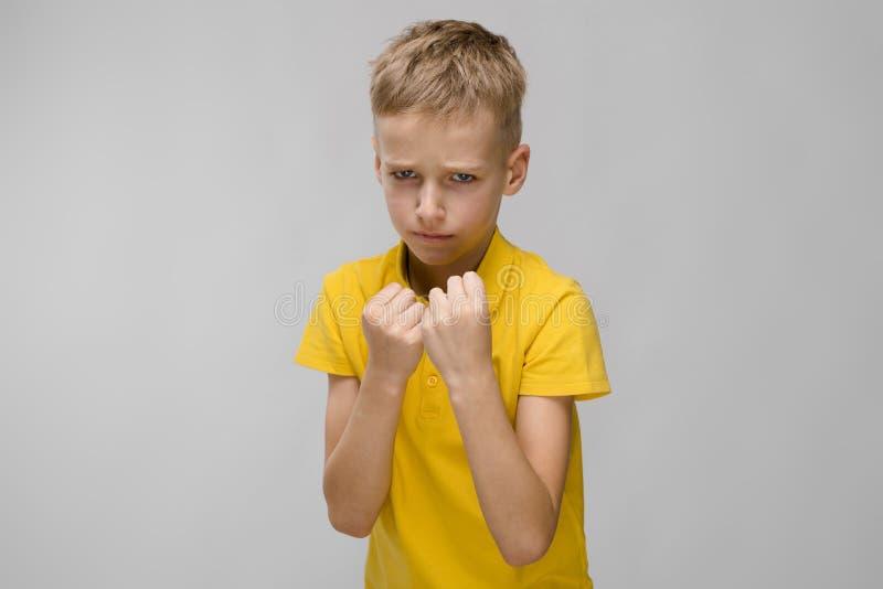 Pequeño muchacho triste serio caucásico rubio en el boxeo amarillo de la camiseta en fondo gris fotografía de archivo libre de regalías